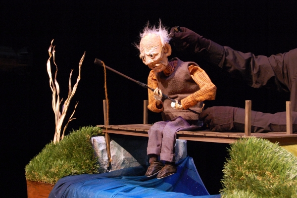 Old Man and the River Promotional Image featuring puppet of an old man fishing.